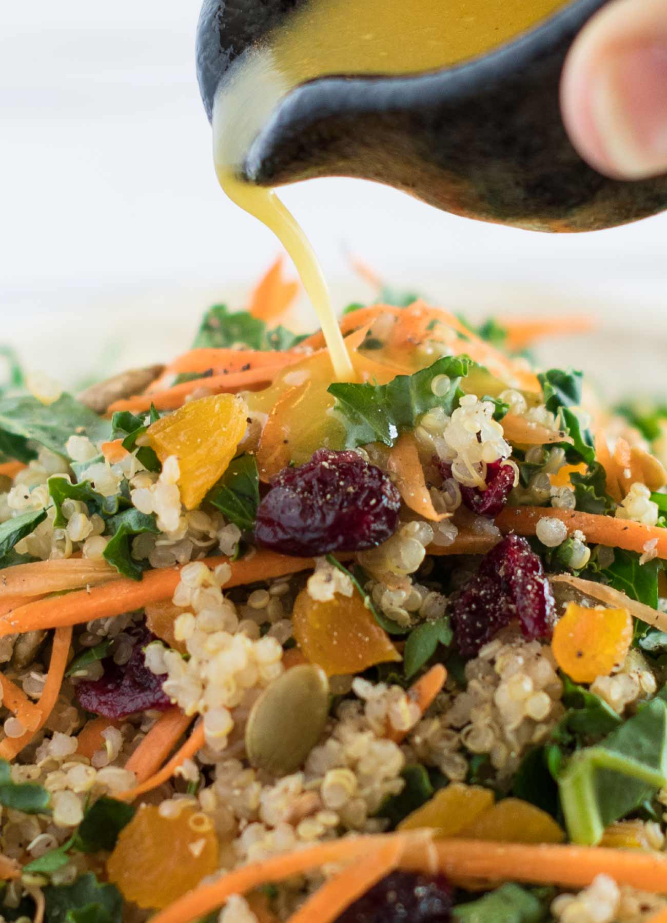 Citrus maple dressing pouring over kale and quinoa salad.