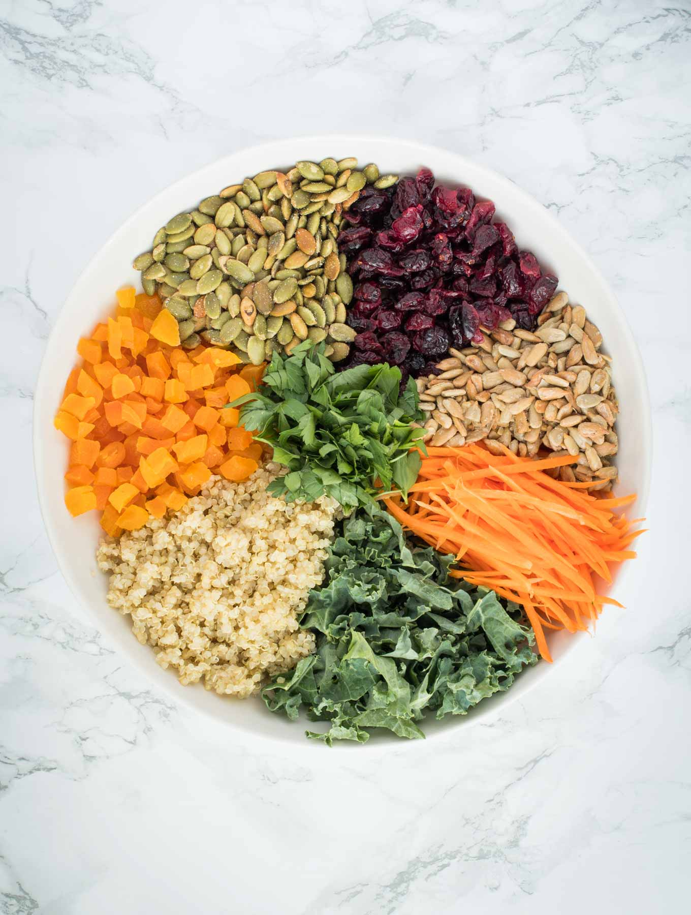 A bowl full of quinoa, dried fruit, seeds, kale, carrots and parsley.