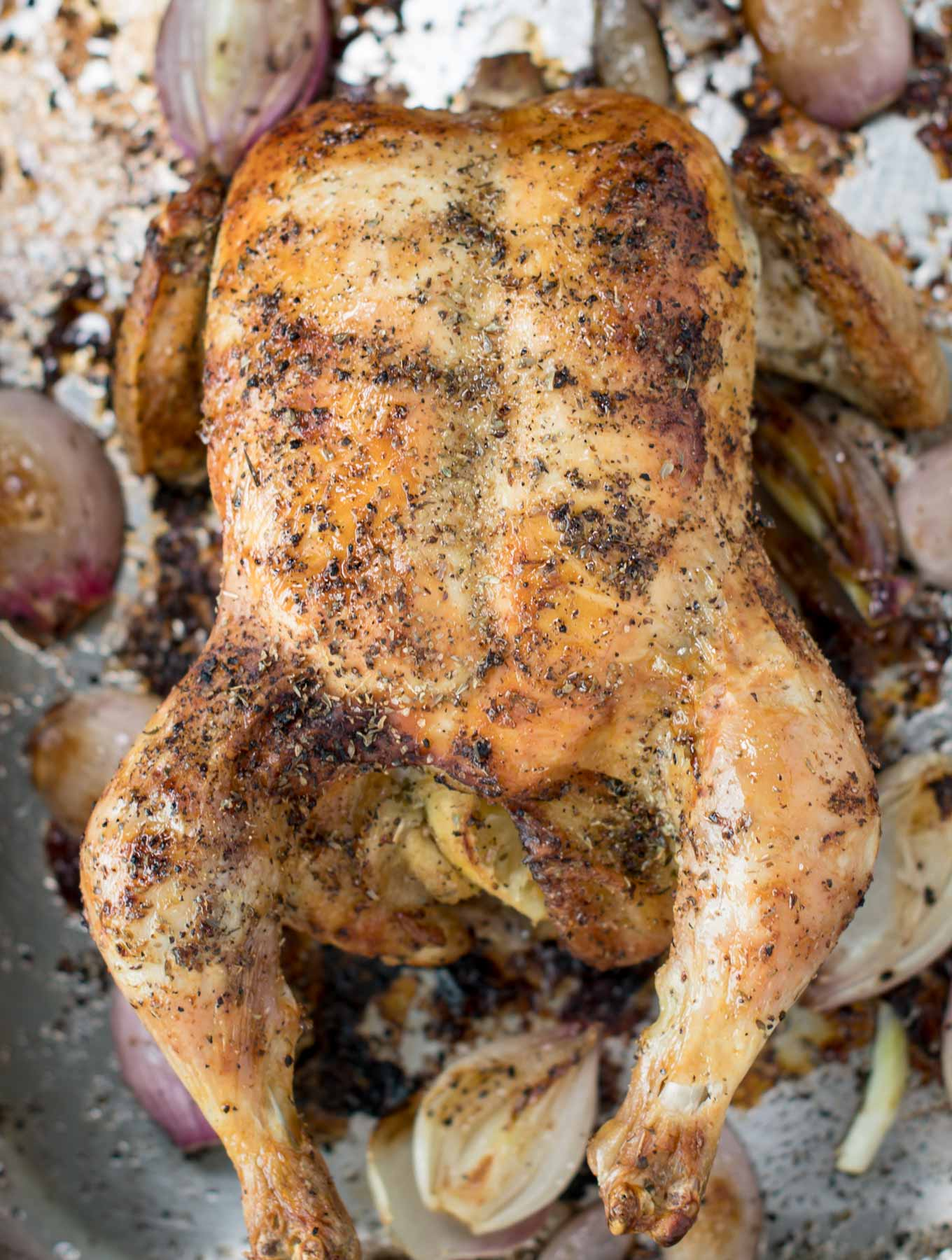 Whole roasted chicken in a roasting pan.