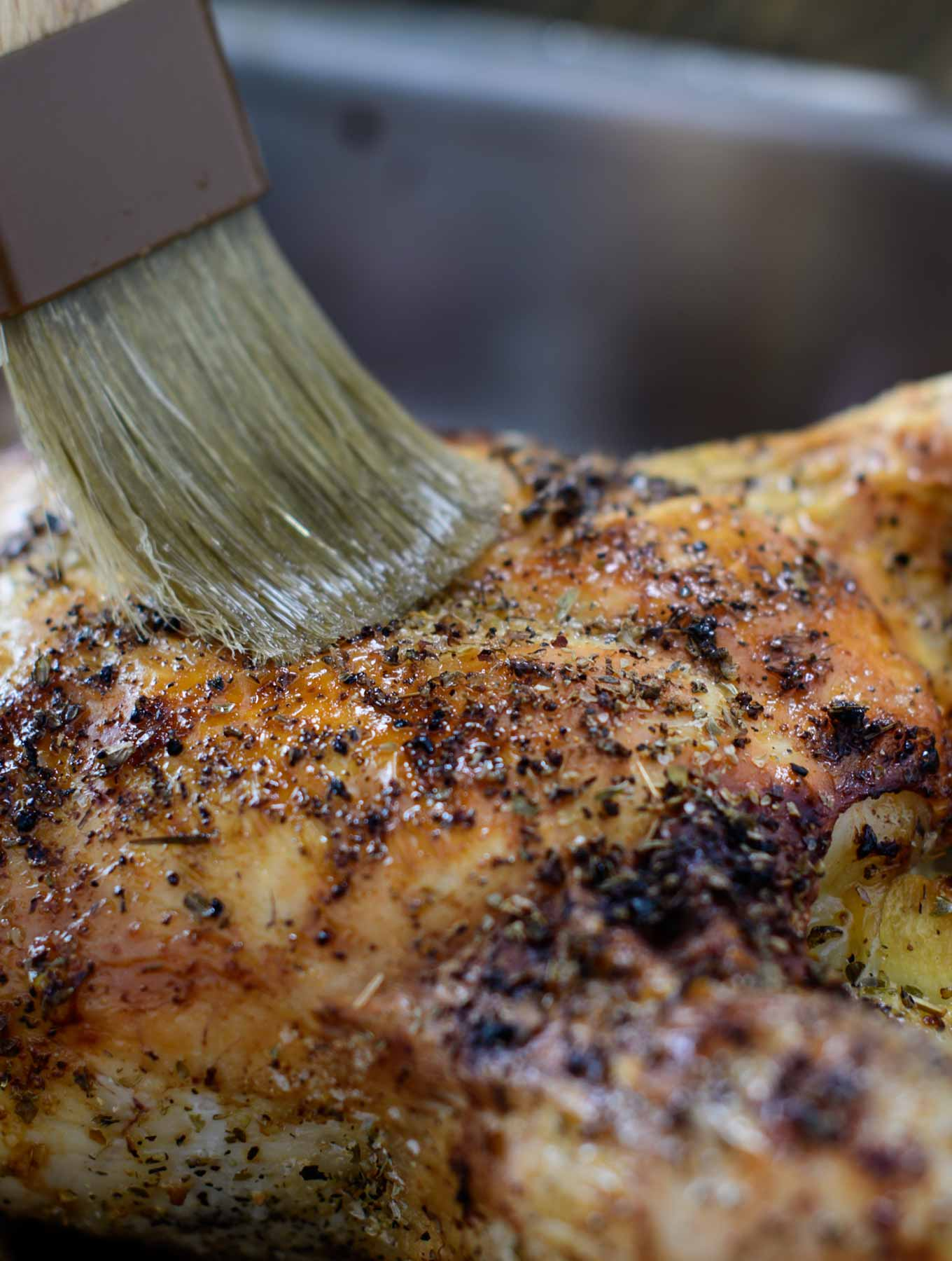 Basting a roasted chicken with white truffle oil
