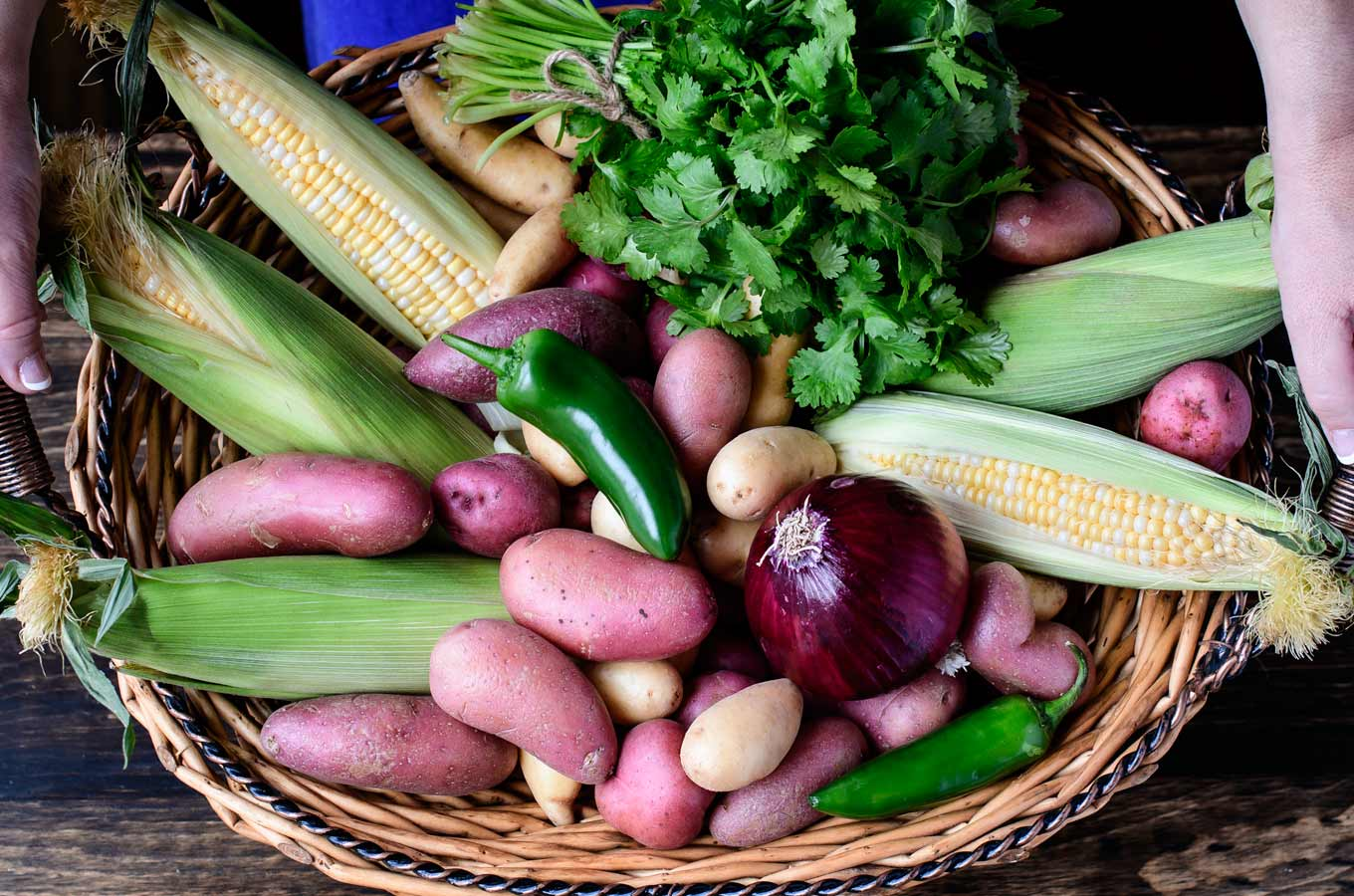 Basket of potatoes, corn, cilantro, red onion and jalapeño