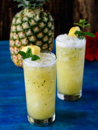 Two pineapple ginger faux-jitos on blue wood board
