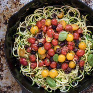 Cast iron skillet of zucchini pasta with tomatoes and olives