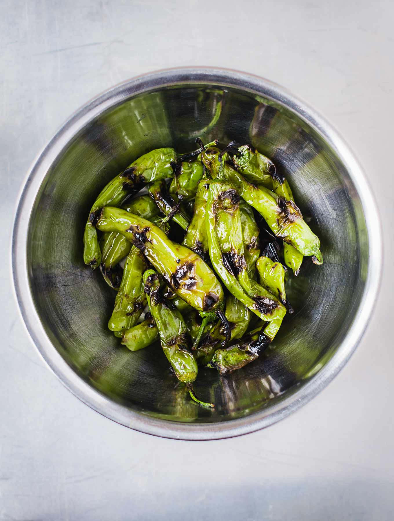 Grilled shishito peppers in stainless bowl