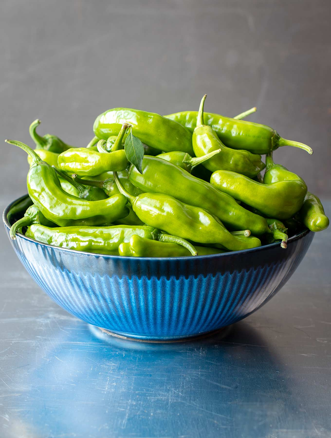 Blue bowl of shishito peppers