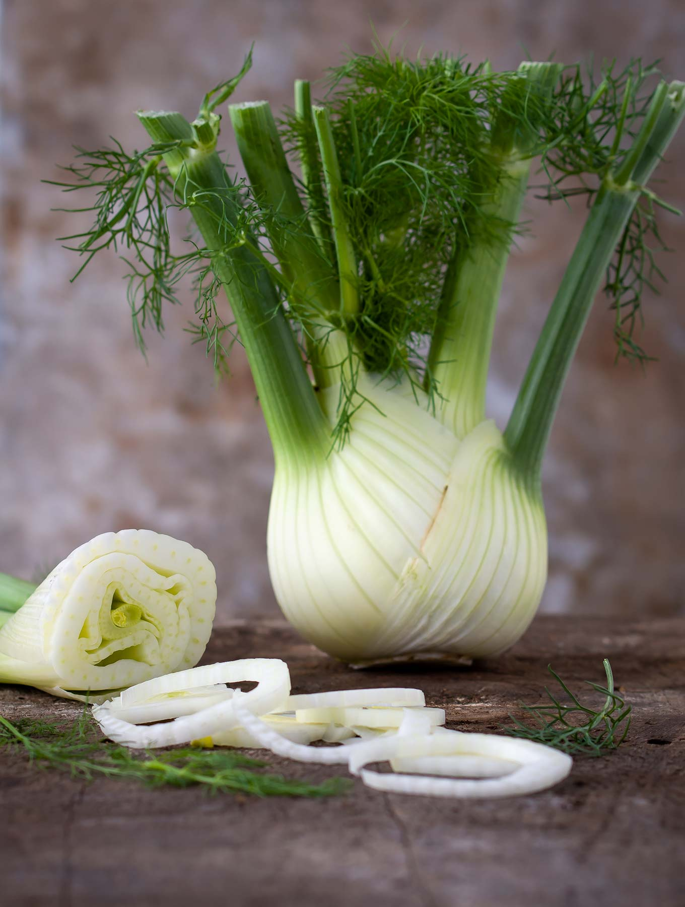 Fennel bulb with cut fennel on a wooden surface