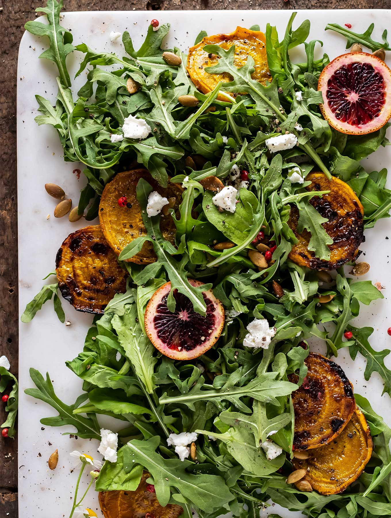 overhead picture of arugula salad with goat cheese and golden beets