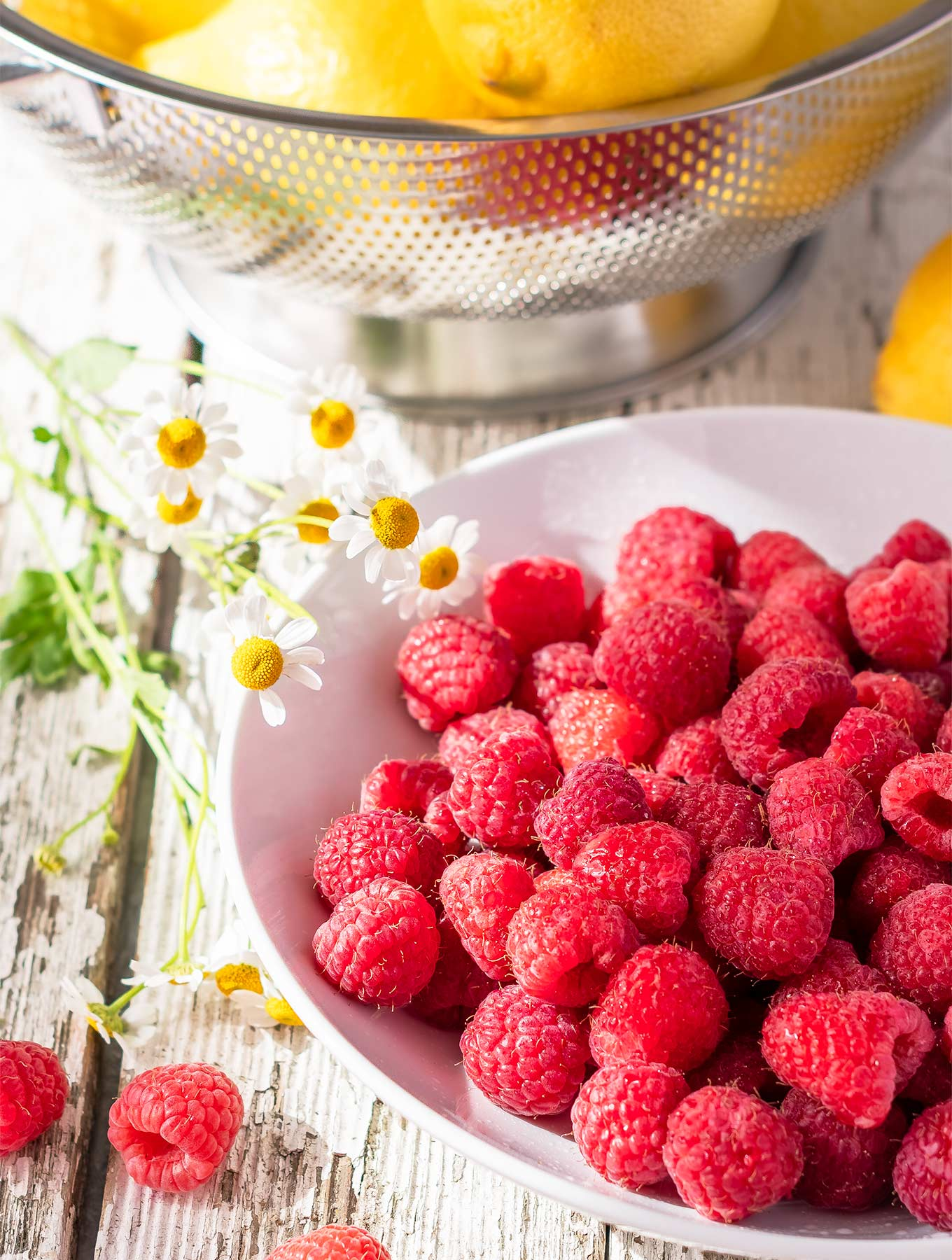 Bowl of fresh raspberries and lemons