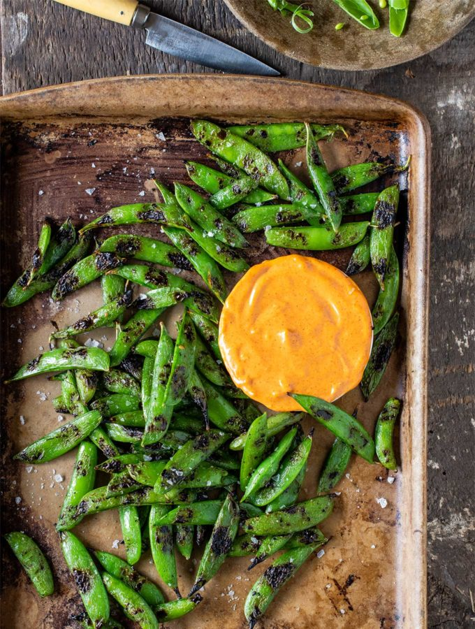 Tray of grilled snap peas with smoked paprika aioli