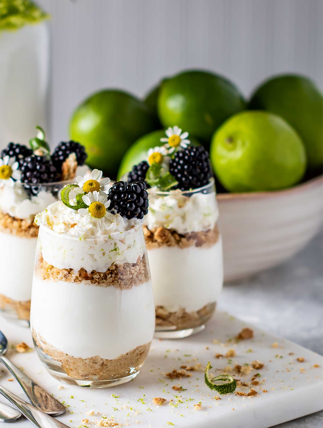 Three glasses of key lime pie parfaits on a marble square