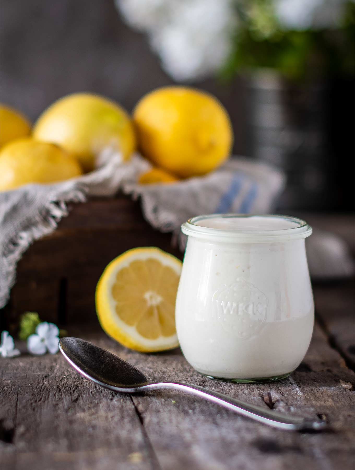 Jar of lemon aioli with fresh lemons on wood board