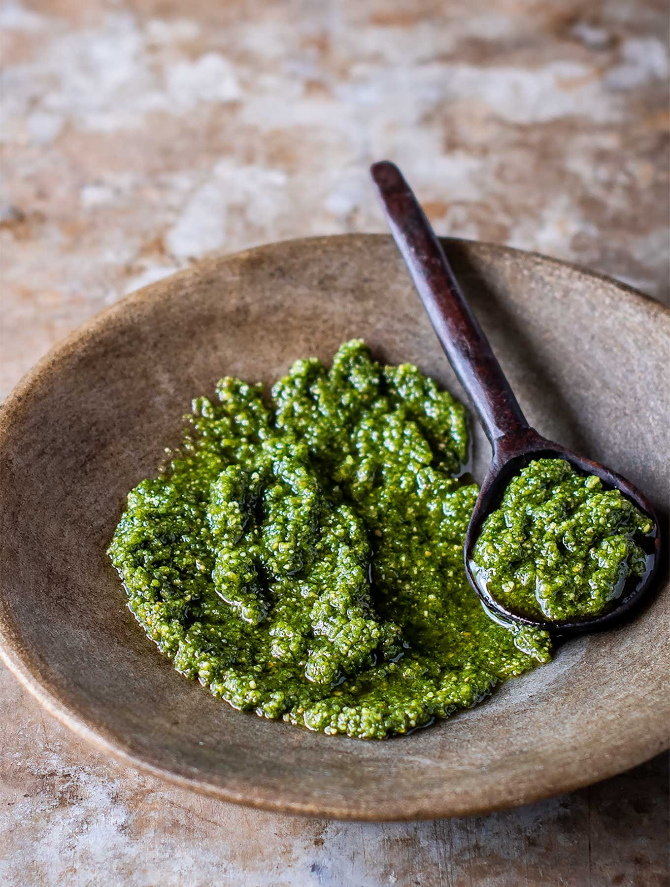 shallow bowl of pumpkin seed pesto with a wooden spoon