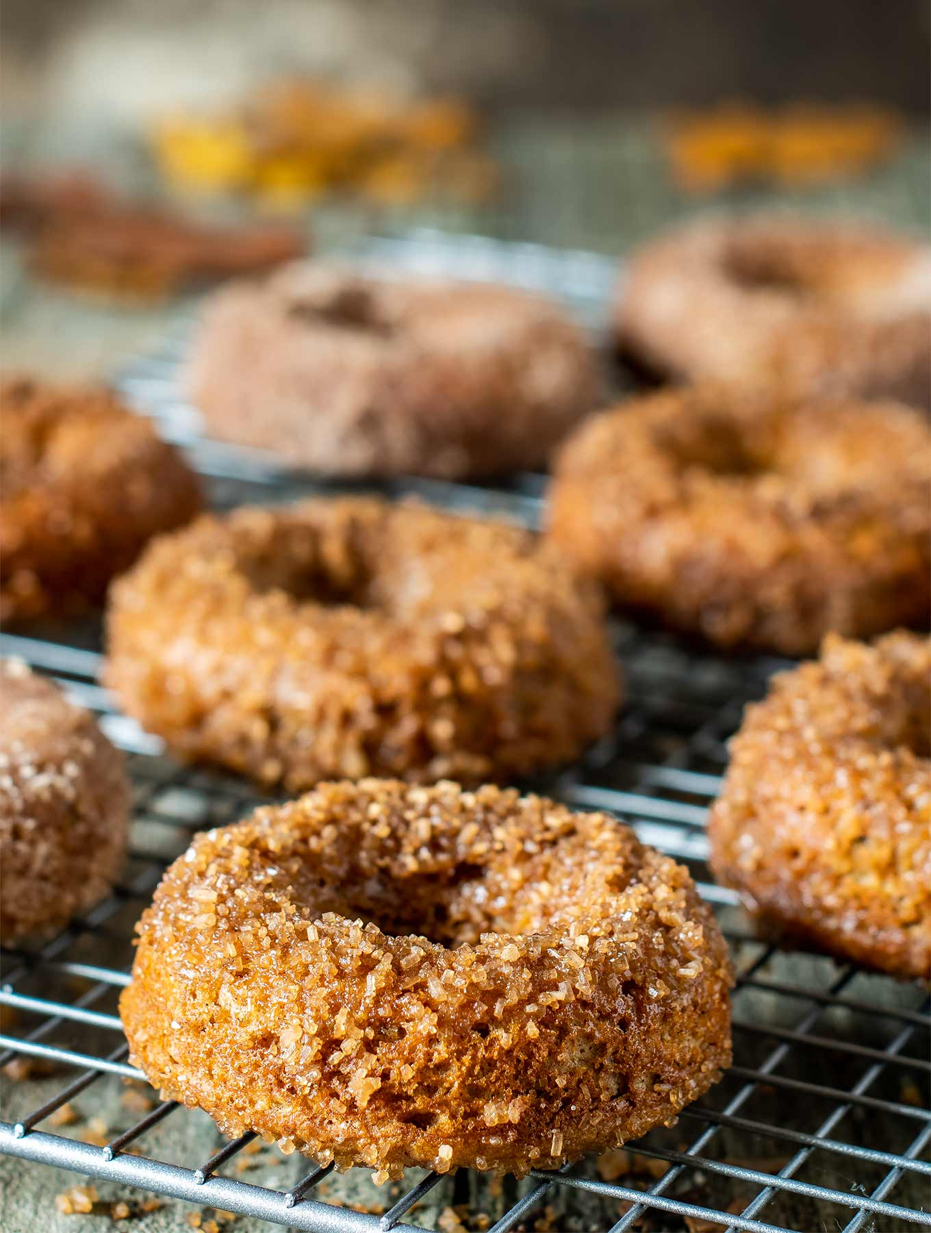 cardamom donuts on a cooling rack with sugar