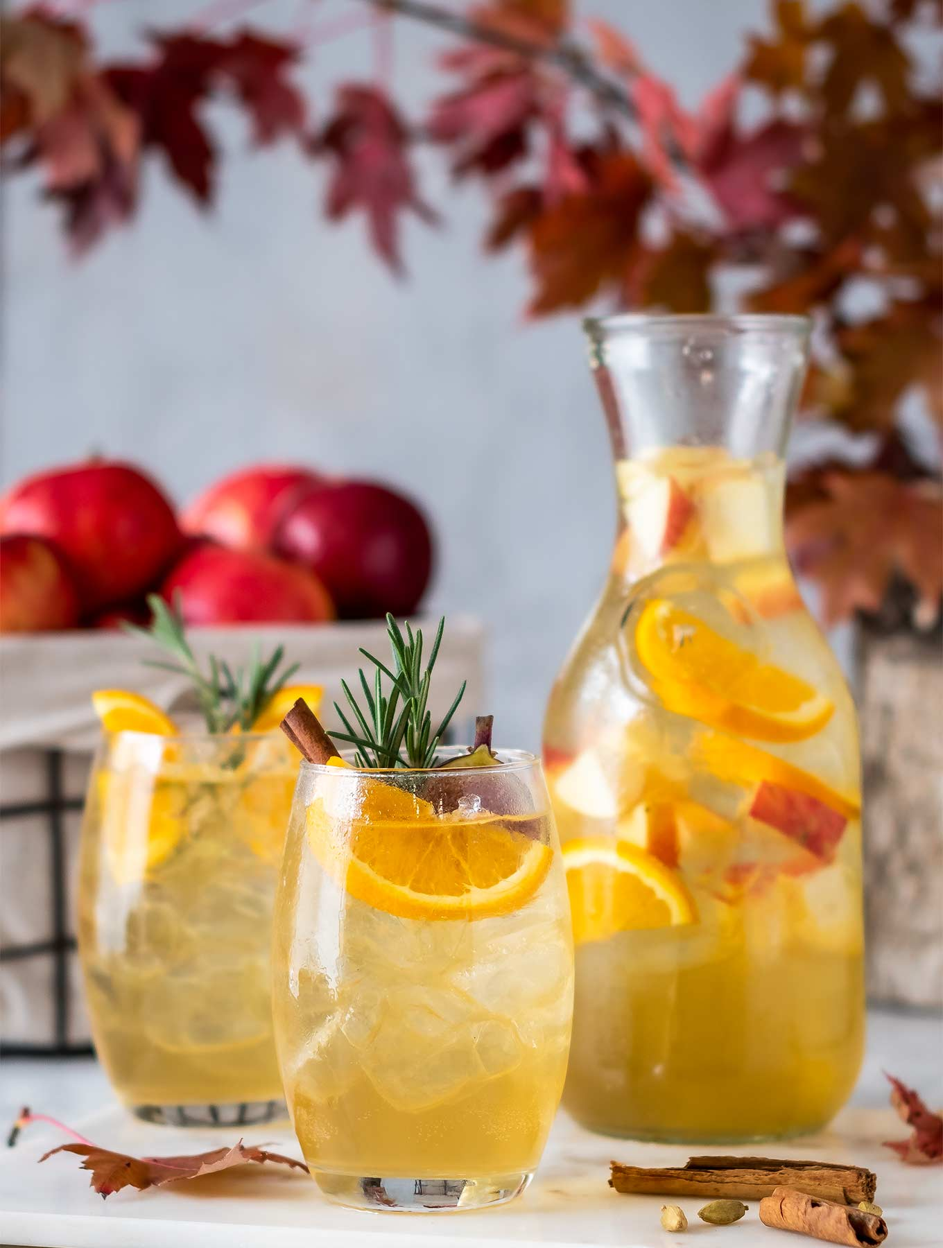 two glasses of fall sangria with a pitcher